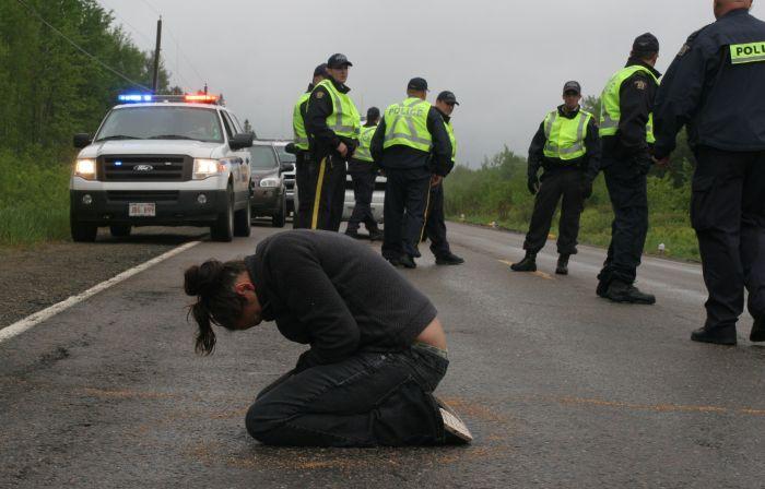 Susanne Patles in prayer, as New Brunswick RCMP confer. [Photo: M. Howe]/Media Coop