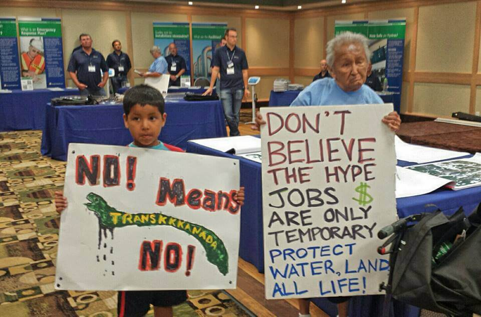 "Nancy Morrison, 85, of Onigaming and Daryl ""Hutchy"" Redsky Jr., 7, of Shoal Lake 40 stand together at Kenora's second Energy East pipeline information session."