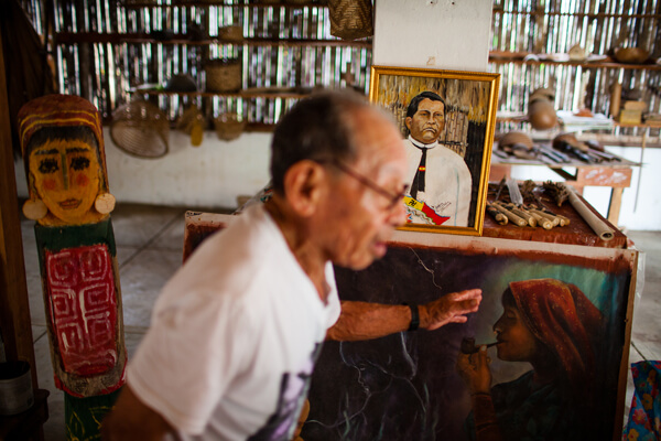 Don Jesús Smith stands in front of a painting of his grandfather, Kuna revolutionary hero Nele Kantule, while talking to students about artifacts in the Olomaili Museum on Ustupu Island. Photo credit: Bear Guerra.