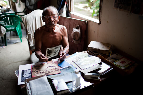 Don Jesús Smith looks through old photos at the desk in his home on Ustupu Island. Don Jesús is the grandson of the Kuna revolutionary leader, Nele Kantule, and an outspoken advocate and teacher who is trying to ensure that young Kuna boys and girls learn about their culture. Photo credit: Bear Guerra