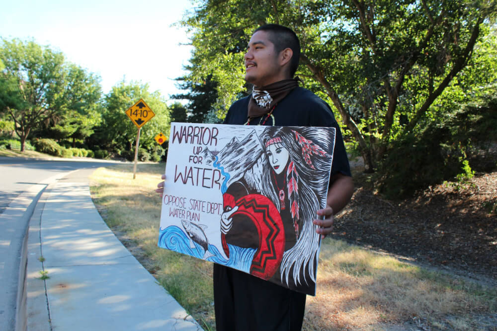 "Gerald Thomas, Elem Pomo, holds up a sign proclaiming, ""Warrior Up For Water."" Photo by Dan Bacher."
