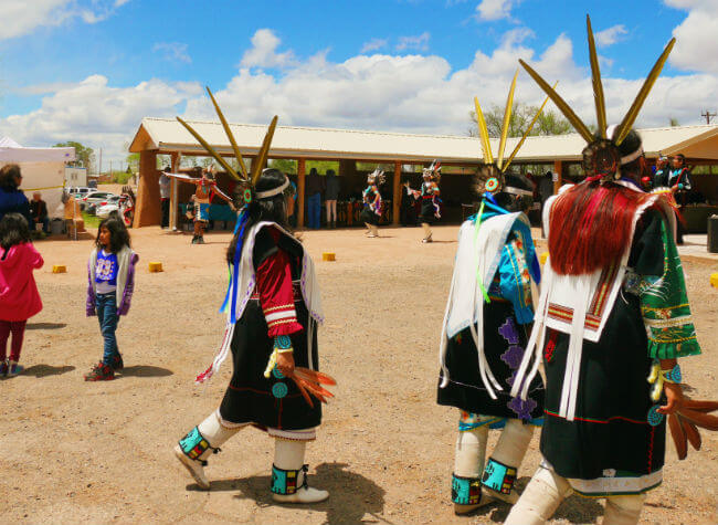 Dancers wearing brightly colored, traditional regalia walk past a dance in progress with artists selling crafts in the background.